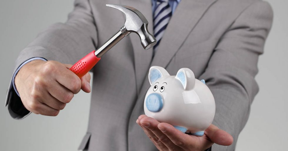 Photo of man in grey suit with blue tie using a hammer to break open a piggy bank.