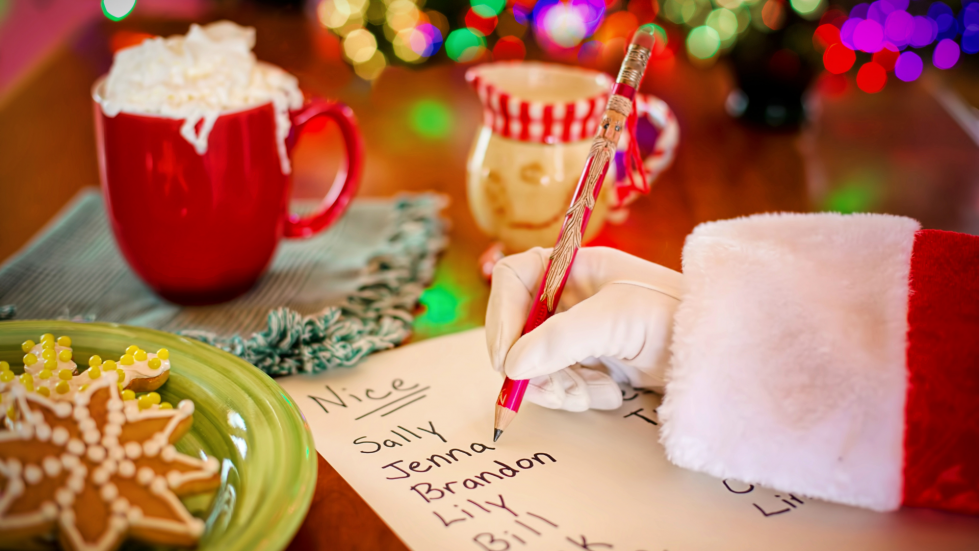 "Close up photo of Santa Claus' hand and arm, writing a ""nice"" list with cookies, milk, lights and a tree in background"