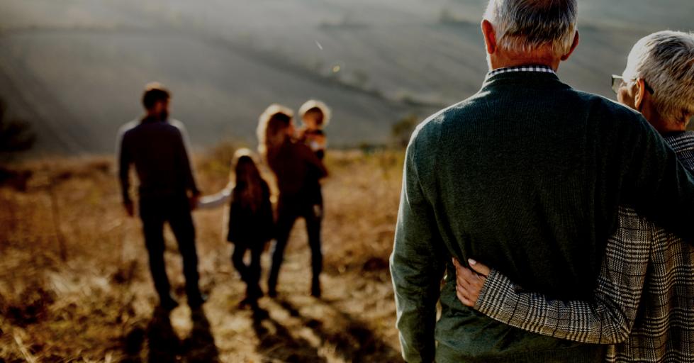 Older couple watch their children and grandchildren walking away