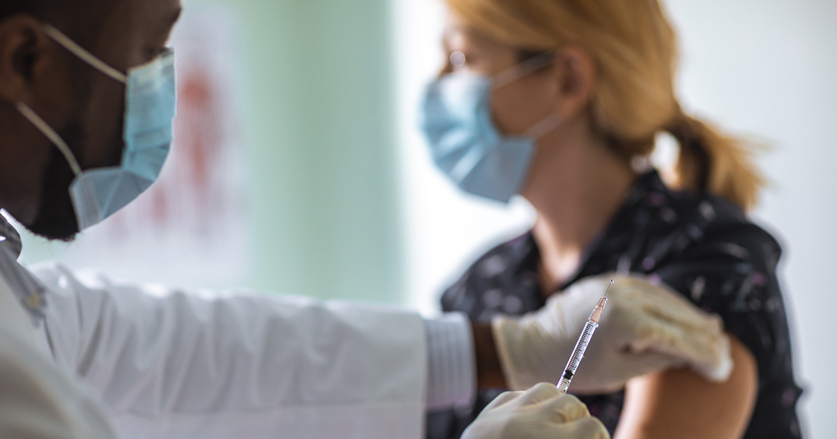 Close up of a young woman getting vaccinated from a man wearing a lab coat